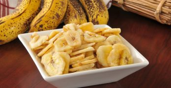 a bowl of dried banana chips on a wooden table after dehydrating bananas