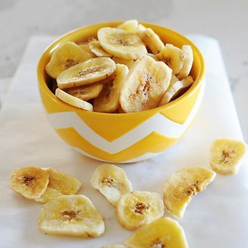 banana chips in a yellow bowl after dehydrating bananas