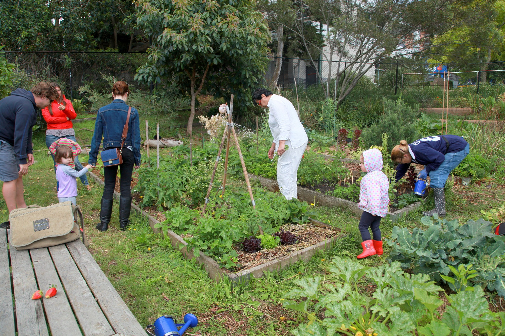 a group of people with their children working together to take care of the community garden