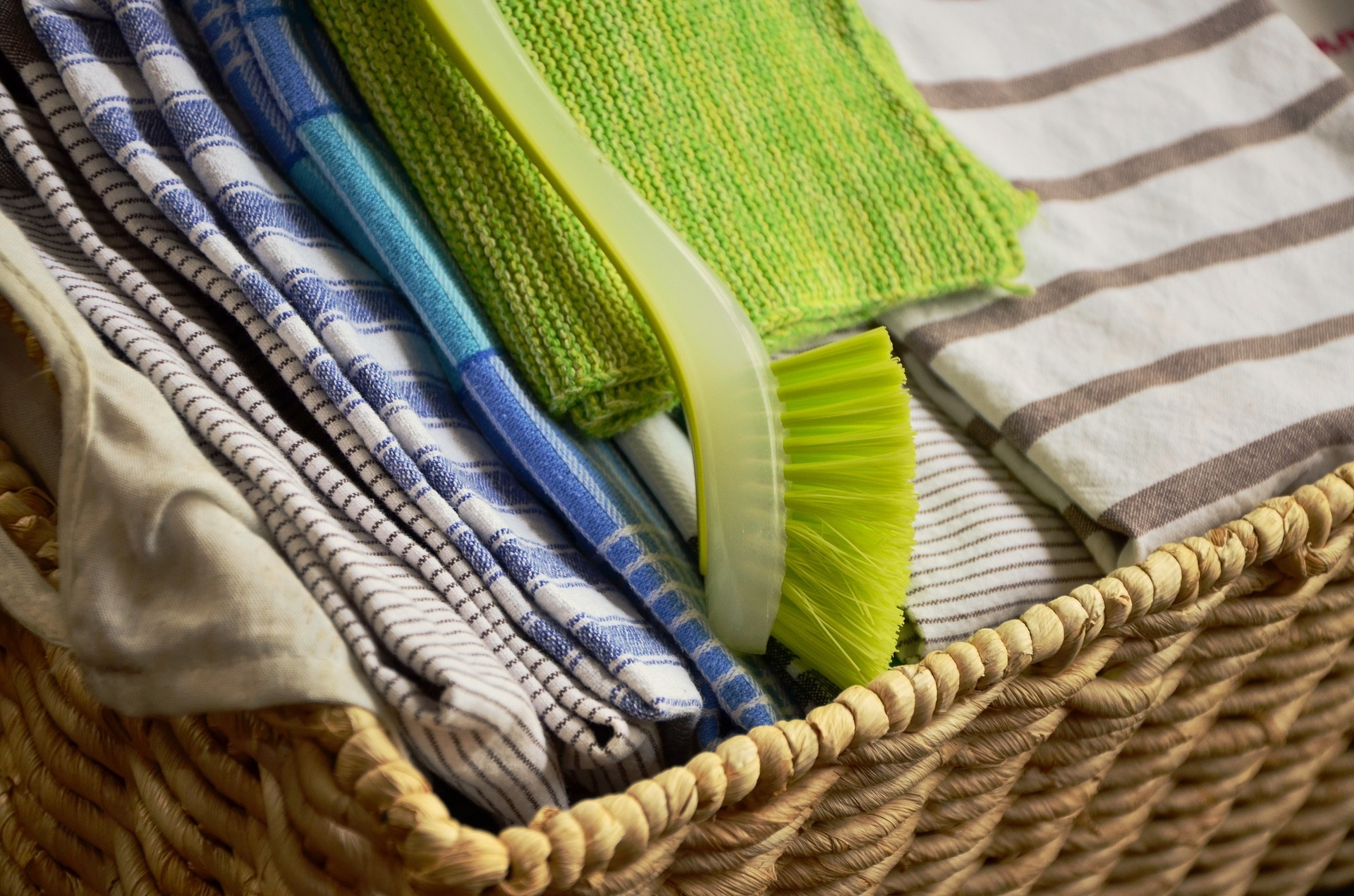 inside the basket are sets of kitchen towel and a green brush