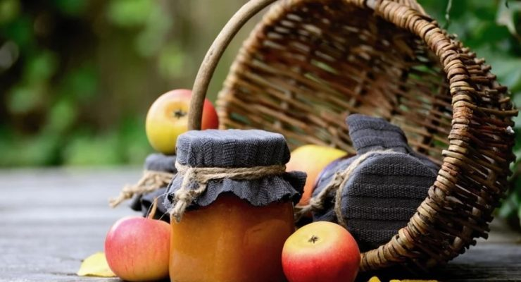 how to can applesauce featured image: a basket overturned with apples and two hand made jars of applesauce