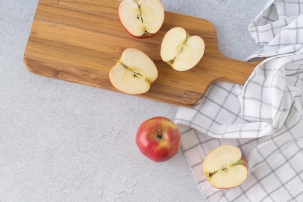 Apples sliced in half, preparing to make applesauce on a cutting board with a whole apple and kitchen towel on a counter